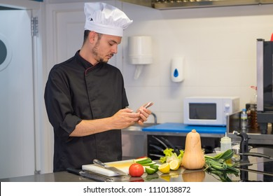 young head chef consulting his recipes on his cell phone through the internet