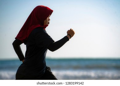 young healthy and active runner Muslim woman in Islam hijab head scarf running and jogging on the beach wearing traditional arab sport clothes in fitness workout and weight loss concept
