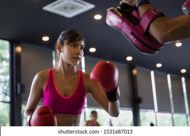 Young healthy Asian woman doing boxing with trainer at the gym, sport and recreation activity concept.