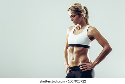 Young healthy athlete woman with perfect body posing in front of camera. Young healthy athlete female posing against white background