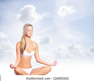 Young, healthy and attractive woman meditating over the sky background