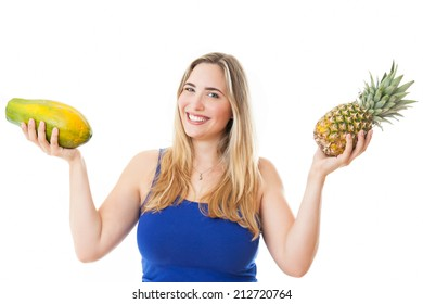 Young healthy beautiful and natural looking woman with a pineapple and a papaya