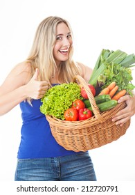 Young healthy beautiful and natural looking woman with a basket full of fresh vegetables