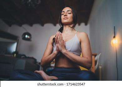 Joven mujer saludable y hermosa en la parte superior deportiva y en las piernas practicando yoga en casa sentada en loto posan en yoga mástil meditando sonriente relajado con los ojos cerrados, concepto de meditación de la atención