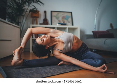 Young healthy beautiful woman in sportive top and leggings practicing yoga at home stretching body on yoga mat smiling relaxed with closed eyes, Healthy Lifestyle Concept