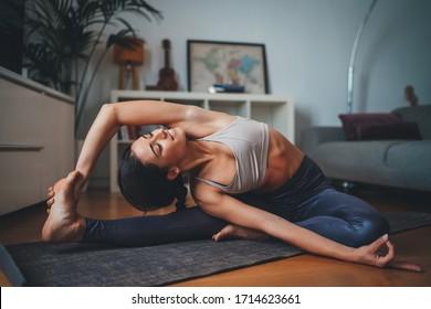Joven mujer saludable hermosa en la parte superior deportiva y en las piernas practicando yoga en casa estirando el cuerpo en la alfombra de yoga sonriendo relajado con los ojos cerrados, Concepto de estilo de vida saludable
