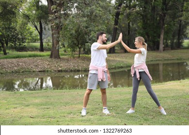 young and healthy couple people enjoying in exercising outdoor and they posting give me five with green trees during summer time in the park