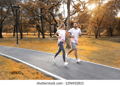 young and healthy couple people are in love jogging in the park during autumn season (healthy or valentine concept)