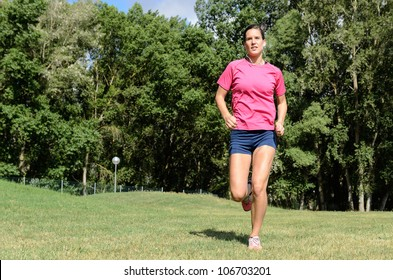 Young healthy female athlete sportswoman running with earphones outdoors in summer.
