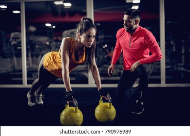 Young healthy focused sporty strong shape girl with a ponytail doing push ups exercises with the kettlebells while handsome helpful personal trainer crouching next to her in the gym.