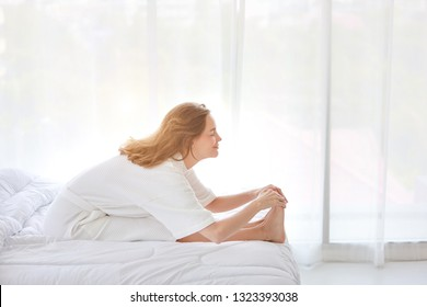 young and healthy girl enjoying in exercising and yoga stretching indoor on bed
