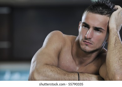 young healthy good looking macho man model athlete at hotel indoor pool