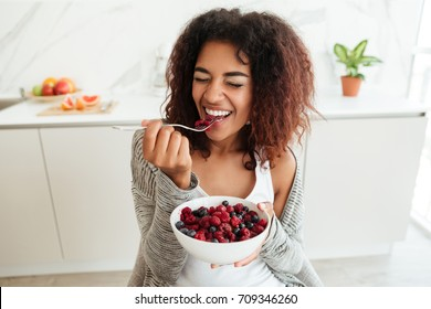 Young healthy laughing african woman eating breakfast and fruits in kitchen in the morning