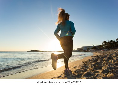 young healthy lifestyle fitness woman running at sunrise beach