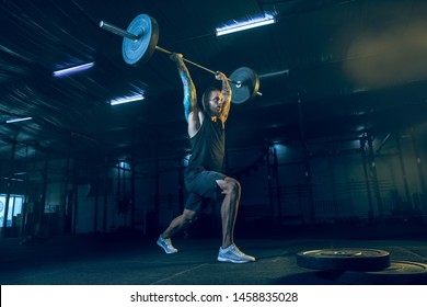Young healthy man athlete doing exercise with the barbell in the gym. Single male model training hard and practicing in lunges. Concept of healthy lifestyle, sport, fitness, bodybuilding.