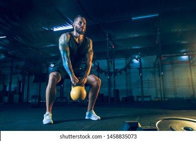 Young healthy man athlete doing exercise with the weights in the gym. Single male model training hard and practicing in squats. Concept of healthy lifestyle, sport, fitness, bodybuilding.