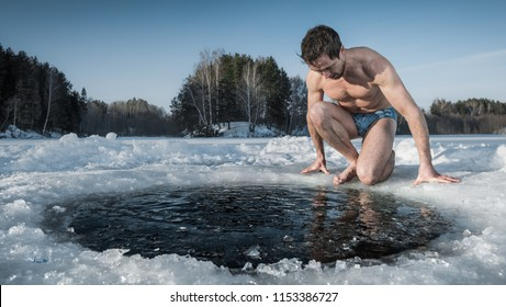 Young healthy man going to swim in an ice hole made in the winter lake