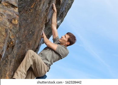 young healthy man rock climbing or bouldering outdoors