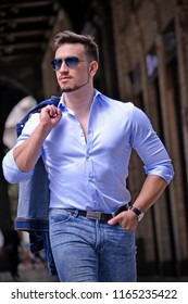 Young healthy man walking on Milan city structure background.