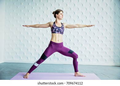 Young healthy muscular woman with dark hair doing yoga on pink mat in white room. Pretty girl dressed in violet leggings with white and black strip and dark top with color print. Yoga lifestyle