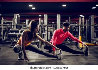 Young healthy sporty active shape girl with a ponytail doing leg stretches on the floor while crouching with a handsome helpful personal trainer next to her in the gym.