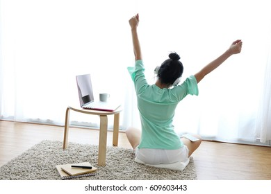Young healthy woman back view at modern home sitting on floor with computer and coffee cup in front of window relaxing in her living room working on internet, Wake up.