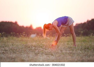 Young healthy woman is doing stretching exercise relaxing and warm up after jogging and running in the nature during beautiful sunset.