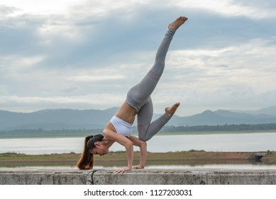 Young healthy woman doing yoga exercises, relax with nature time.