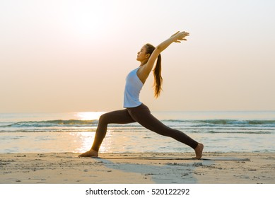 Young healthy woman practicing and workout yoga on the beach at sunrise, benefits of natural environments for physical activity.