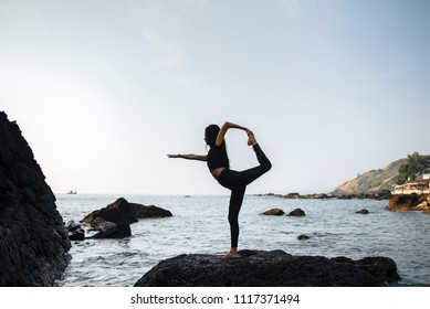 Young healthy woman practicing yoga on the beach at sunset.