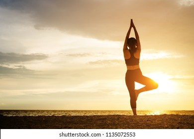 Young healthy woman practicing yoga on the beach exercise at sunset time. healthy concept.