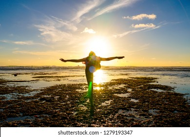 Young healthy woman practicing yoga on the beach at sunset. Strong confidence woman under the sunset at seaside. Silhouette of young woman doing yoga on the beach.