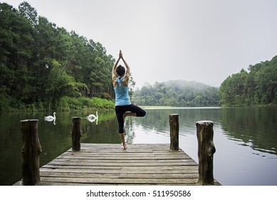 Young healthy woman practicing yoga on the bridge in the nature. Healthy Concept.