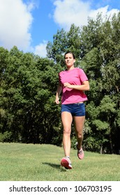 Young and healthy woman running with earphones outdoors in summer. Sportswoman marathon runner.