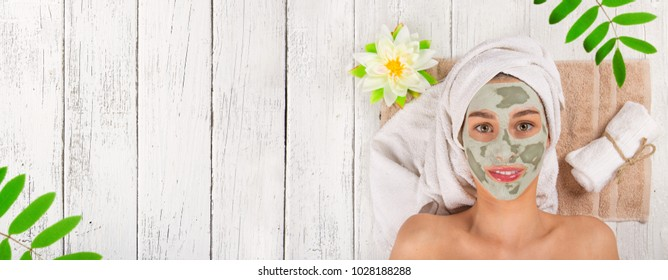 Young healthy woman in spa making treatments and face clay mask.
