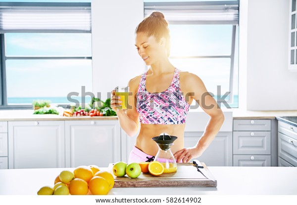 Young healthy woman standing in sunlight with glass of orange juice. Horizontal indoors shot