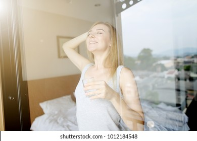 young healthy woman is stretching after sleep with glass of water, drink every day. Shoot from window, concept of healthy habits