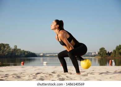 Young healthy woman training upper body with weights at the beach. Single caucasian female model training air at the river side in sunny day. Concept of healthy lifestyle, sport, fitness, bodybuilding