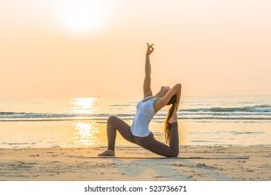 Young healthy Yoga woman workout yoga pose on the beach at sunrise, benefits of natural environments for physical, spiritual, healthy, relaxing concept.