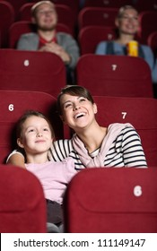 Young with her mother watching a movie at the cinema