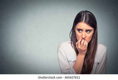 Young hesitant nervous woman biting her fingernails craving something or anxious, isolated on gray wall background with copy space. Negative human emotions facial expression feeling