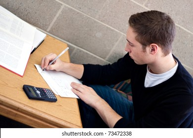 A young high school or college student working on his math homework.