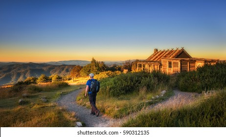 Young hiker with backpack approaching Craigs Hut, built as the the set for Man from Snowy River movie in the Victorian Alps, Australia