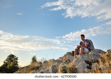 Young hiker with backpack sitting relaxing on a rock on the top of a mountain