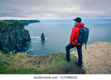 Young hiker with a backpack standing at the cliffs of Moher located at the edge of the Burren region in County Clare, Ireland.