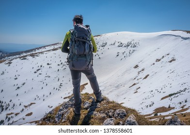 Young hiker with a backpack standing on top of a Suchy vrch hill looking at a valley under Ostredok hill in Velka Fatra national park in Slovakia in winter