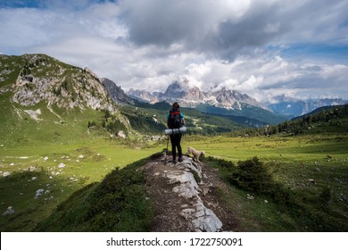 Young hiker with backpack walking on the mountain trail with dog