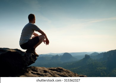 Young hiker in black pants and shirt  is sitting on cliff's edge and looking to misty hilly valley bellow. Enjoy life.Hiker sitting. Outdoor man enjoy.Cliff edge. Looking over horizon edge. Hike man.