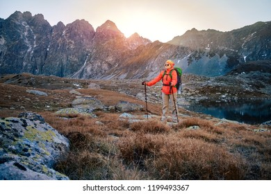 Young hiker in colorful fantastic mountain landscape at gold sunset near Hincovo Pleso lake in High tatras
