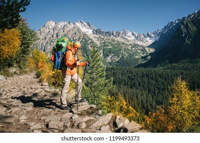 Young hiker in colorful fantastic mountain landscape at gold autumn near Rysy peak in High Tatras